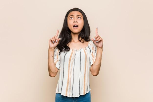 Jovem adolescente chinês bonito mulher loira jovem vestindo um casaco contra uma parede rosa apontando para cima com a boca aberta.