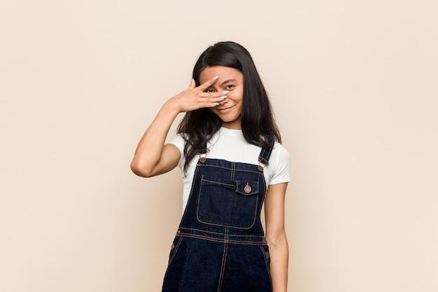 Jovem adolescente chinês bonito mulher loira jovem vestindo um casaco contra uma parede rosa piscar através dos dedos, rosto de vergonha coberta.