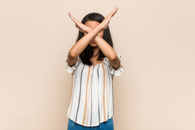Jovem adolescente chinês fofo jovem mulher loira vestindo um casaco contra um espaço rosa, mantendo os dois braços cruzados, conceito de negação.