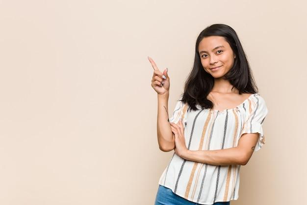 Jovem adolescente chinês fofo jovem mulher loira vestindo um casaco contra um fundo rosa, sorrindo alegremente, apontando com o dedo indicador para longe.