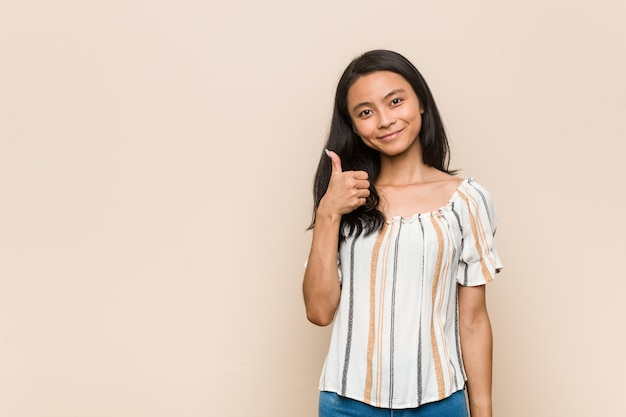 Jovem adolescente chinês fofo jovem mulher loira vestindo um casaco contra uma parede rosa, sorrindo e levantando o polegar