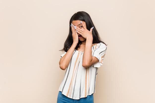 Jovem adolescente chinesa bonitinha mulher loira jovem vestindo um casaco contra uma parede rosa pisca entre os dedos, assustada e nervosa.