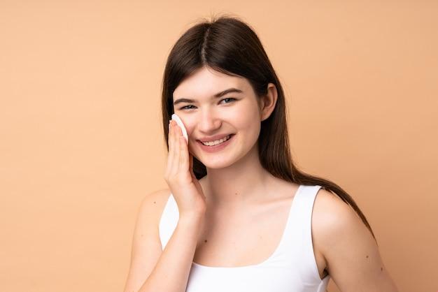 Jovem adolescente com almofada de algodão para remover a maquiagem do rosto