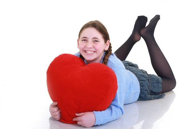 Jovem adolescente com coração vermelho isolado no fundo branco
