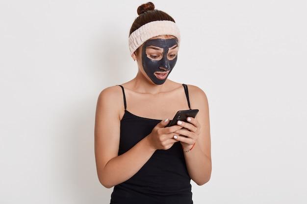 Jovem adolescente com máscara facial preta no rosto, usando seu telefone inteligente, olhando para a tela do dispositivo com expressão facial de surpresa, garota fazendo procedimentos cosméticos.