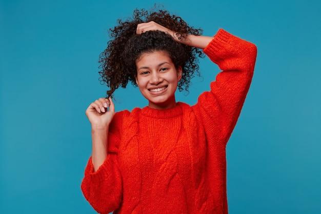 Jovem adolescente com suéter vermelho e rosto feliz e bonito
