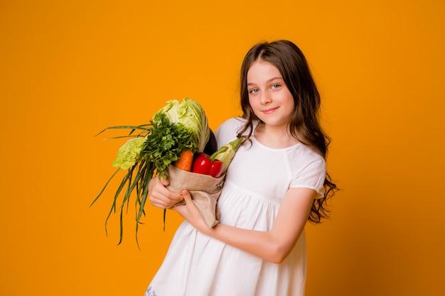 Jovem adolescente com um saco de legumes