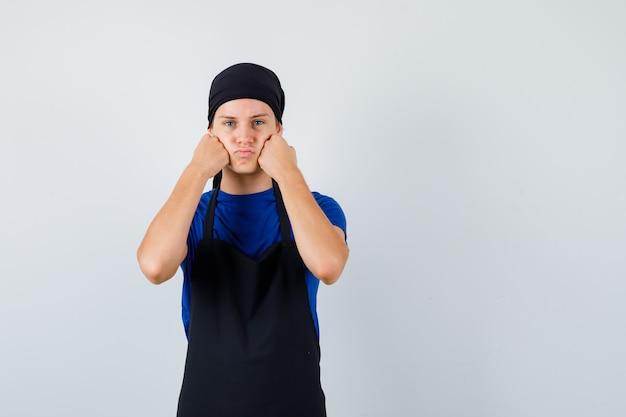 Jovem adolescente cozinheiro amuado com as bochechas apoiadas nos punhos em t-shirt, avental e olhando pensativo. vista frontal.