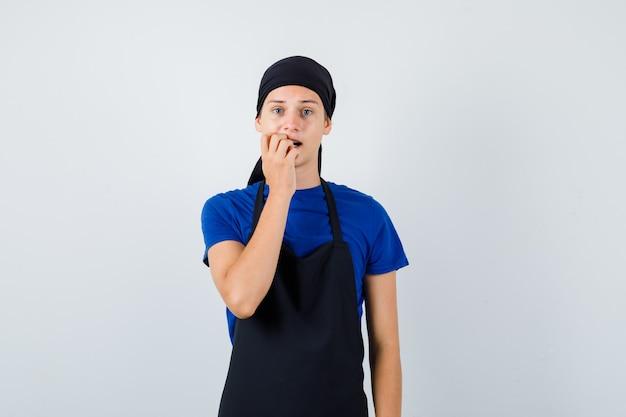 Jovem adolescente cozinheiro em t-shirt, avental roendo unhas emocionalmente e olhando com problemas, vista frontal.