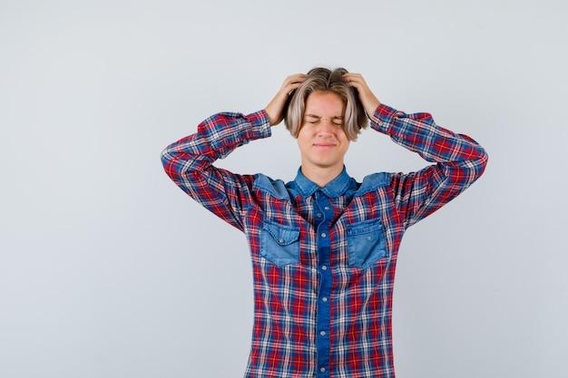 Jovem adolescente de camisa xadrez com as mãos na cabeça e parecendo angustiado