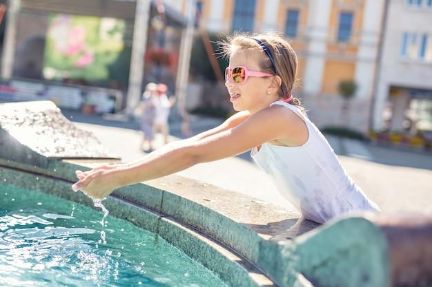 Jovem adolescente de óculos espirra água de uma fonte na cidade em um dia quente de verão.