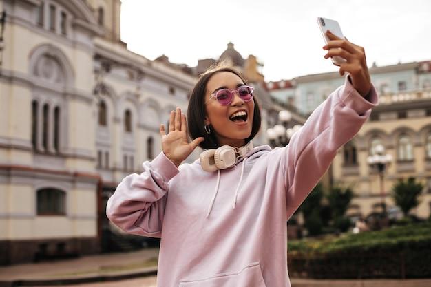 Jovem adolescente descolada com capuz rosa e óculos de sol elegantes tira uma selfie, segura o telefone e faz poses com fones de ouvido do lado de fora