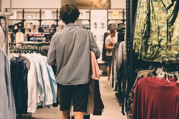 Jovem adolescente do sexo masculino andando no conceito de compras de loja de roupas casuais