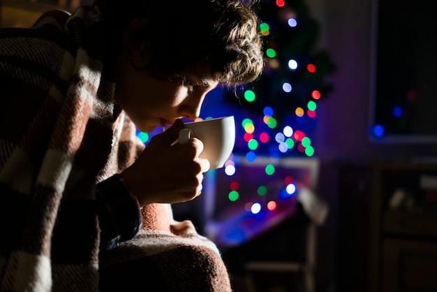 Jovem adolescente doente, bebendo a xícara de chá quente debaixo do cobertor, luta contra a doença em casa durante a noite.