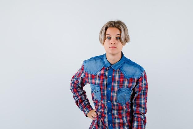 Jovem adolescente em camisa xadrez, mantendo a mão na cintura e parecendo perplexo, vista frontal.
