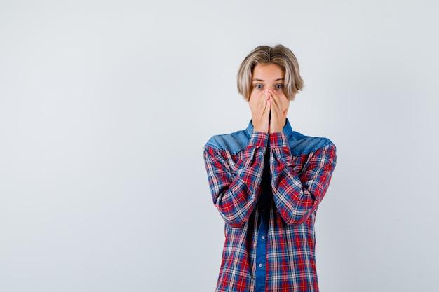 Jovem adolescente em camisa xadrez, mantendo as mãos na boca e parecendo assustado, vista frontal.