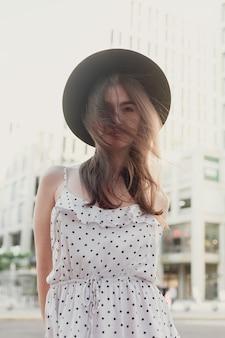 Jovem adolescente em um vestido branco e um chapéu. estilo da cidade grande. céu do sol e os raios do sol. mulher bonita de beleza natural com chapéu fedora hipster preto, na noite quente de verão, pôr do sol na cidade grande