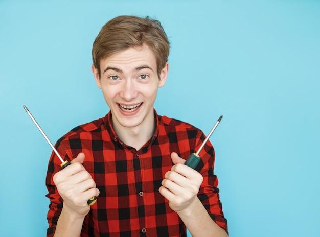 Jovem adolescente emocional sorridente, de camisa vermelha em fundo azul, com uma chave de fenda