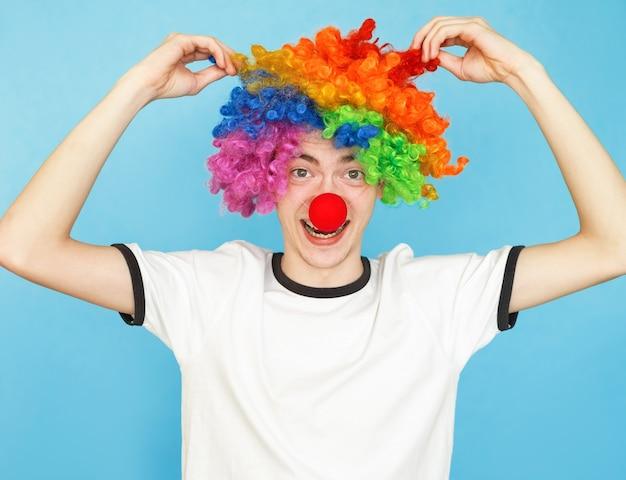 Jovem adolescente engraçado do sexo masculino com camiseta branca sobre fundo azul e peruca de palhaço