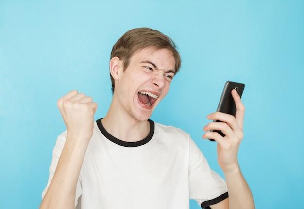 Jovem adolescente engraçado do sexo masculino com uma camiseta branca sobre fundo azul olhando para o smartphone como se tivesse ganhado alguma coisa