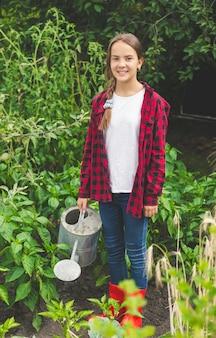Jovem adolescente feliz posando com um regador no jardim