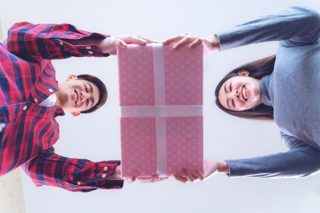 Jovem adolescente feminino e bonito homem segurando grande presente