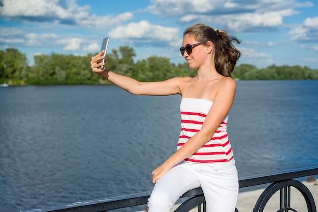 Jovem adolescente grava vídeo em um smartphone