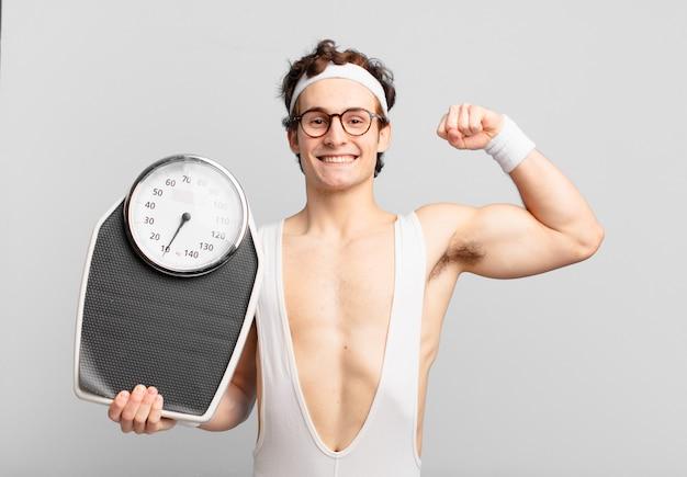 Jovem adolescente jovem atleta maluco comemorando uma vitória bem-sucedida e segurando uma balança