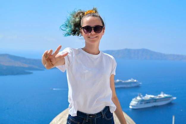 Jovem adolescente linda garota turista posando sorrindo, paisagem ensolarada de fundo do mar com navios de cruzeiro brancos no mar egeu, na famosa ilha grega de santorini