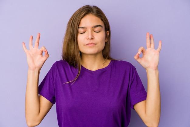Jovem adolescente magrinha caucasiana em fundo roxo relaxa após um duro dia de trabalho, ela está realizando ioga.