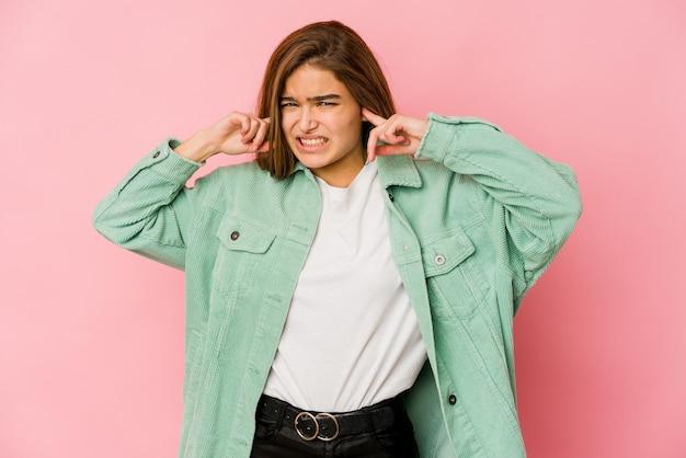 Jovem adolescente magrinha cobrindo as orelhas com os dedos, estressada e desesperada por um ambiente barulhento