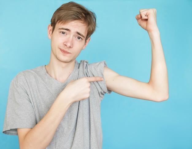 Jovem adolescente masculino engraçado em camiseta cinza na parede azul mostra seus músculos, após perda de peso, piada, humor