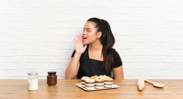 Jovem adolescente menina asiática com muitos bolo de muffin gritando com a boca aberta