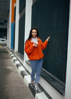 Jovem adolescente na moda anda pela cidade e bebe café