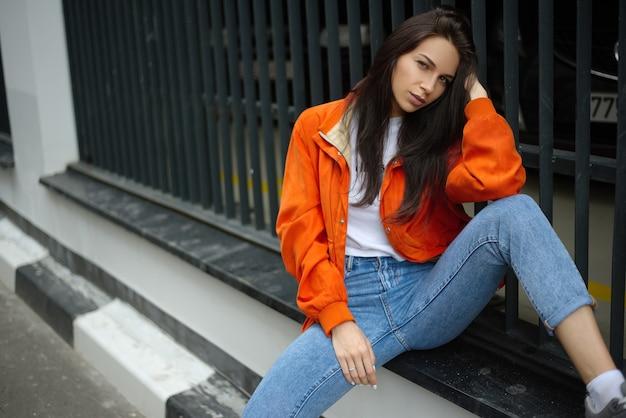 Jovem adolescente na moda caminha pela cidade no verão com uma jaqueta da moda e jeans