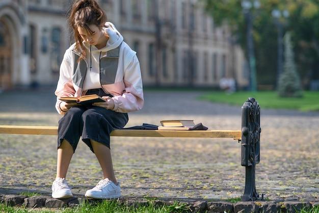 Jovem adolescente na moda sentada estudando