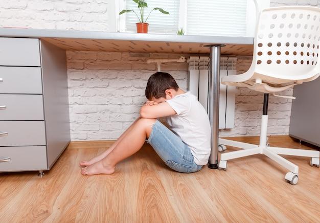 Jovem adolescente pré-adolescente caucasiano sentado sob a mesa