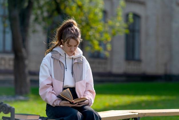 Jovem adolescente relaxando lendo em um parque