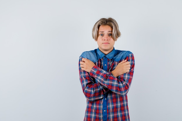 Jovem adolescente se abraçando, sentindo frio em uma camisa xadrez e parecendo indefeso. vista frontal.