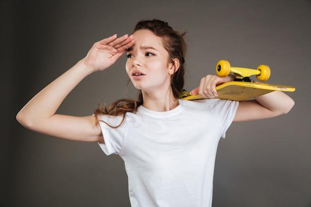 Jovem adolescente segurando o skate e olhando para a distância