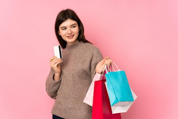 Jovem adolescente segurando sacolas de compras e cartão de crédito