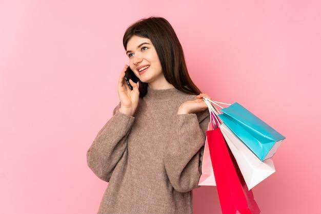 Jovem adolescente segurando sacolas de compras e chamando um amigo com seu telefone celular