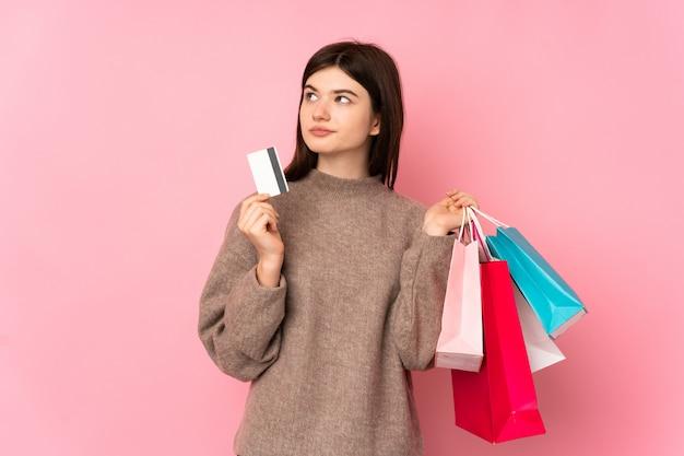 Jovem adolescente segurando sacolas de compras e um cartão de crédito e pensando