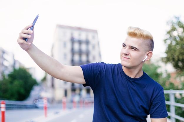 Jovem adolescente sentado ao ar livre enquanto estiver a tomar uma selfie