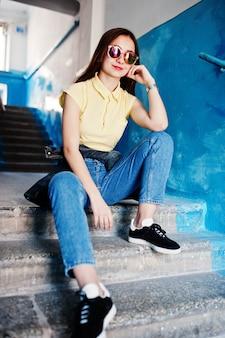 Jovem adolescente sentado nas escadas da entrada da casa, usar t-shirt amarela, jeans e óculos de sol.