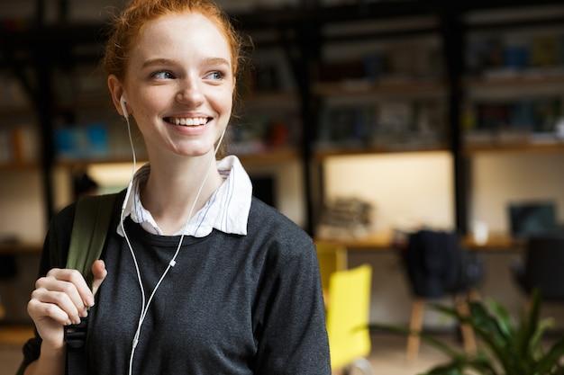Jovem adolescente sorridente com fones de ouvido carregando uma mochila