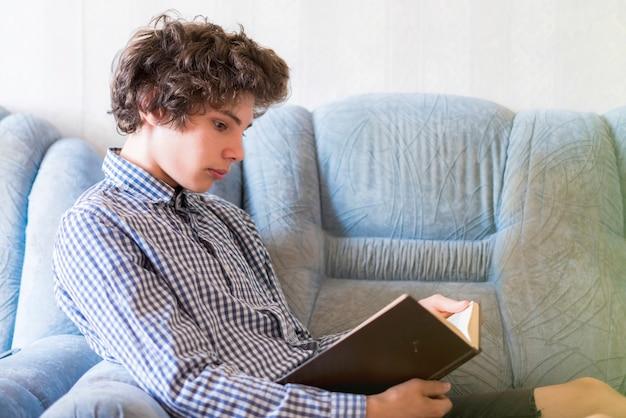 Jovem adolescente sorridente, deitado no sofá e lendo um livro em casa