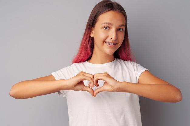 Jovem adolescente tocando seu coração com as mãos sobre fundo cinza
