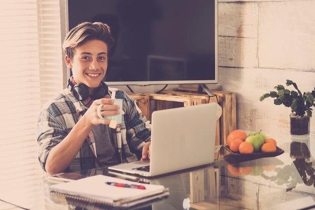 Jovem adolescente trabalhando em casa em silêncio com fones de ouvido - ouça música enquanto faz a lição de casa e bebe - o fundo da casa e muitas frutas na mesa