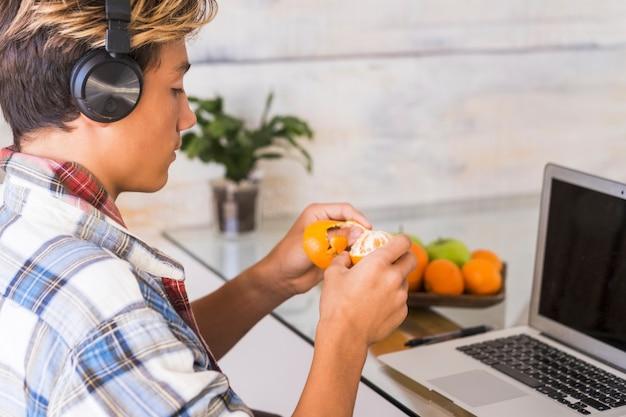 Jovem adolescente trabalhando em casa em silêncio com fones de ouvido - ouvir música enquanto faz a lição de casa e comendo uma laranja - fundo de casa e muitas frutas na mesa